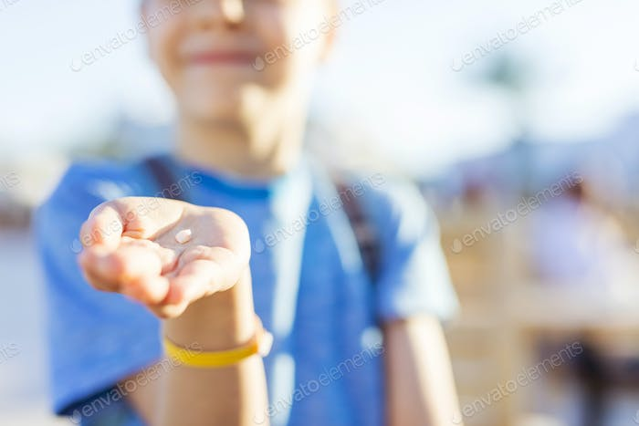 Junge zeigt einen Zahn, den er gerade verloren hat