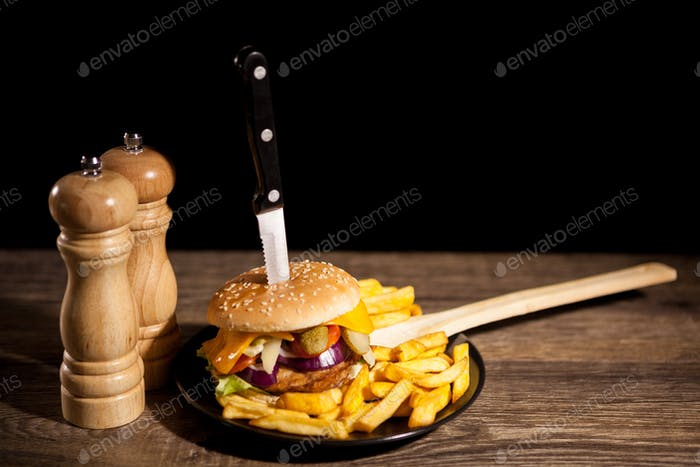 Classic home made cheesburgers on black plate and background