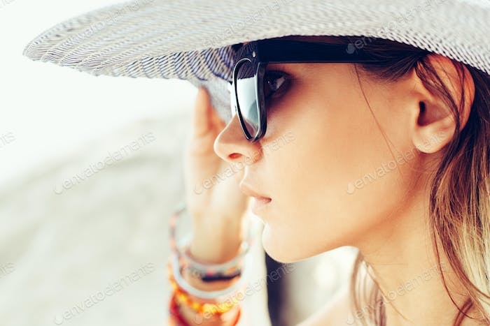 Face of young woman wearing hat and sunglasses