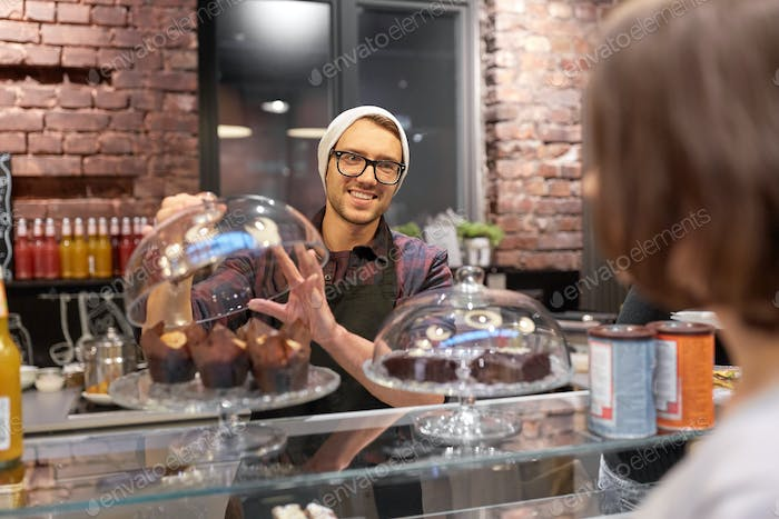 man or barman with cakes serving customer at cafe