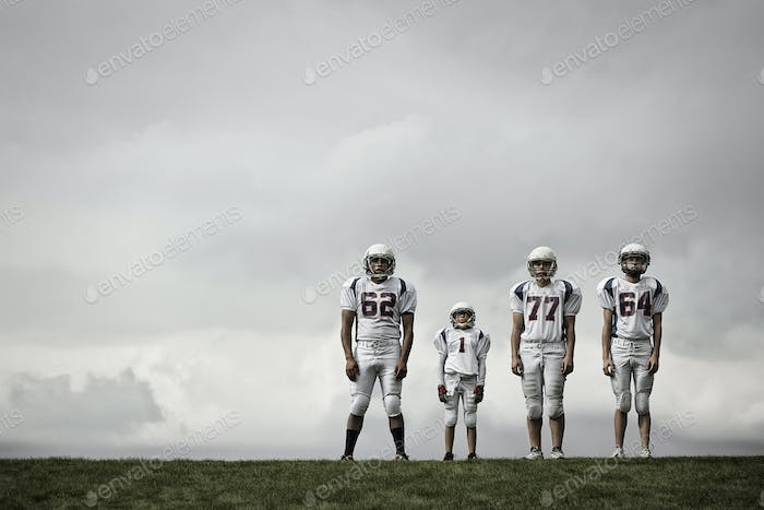 A group of four football players in sports uniform, three tall figures and one shorter team player.