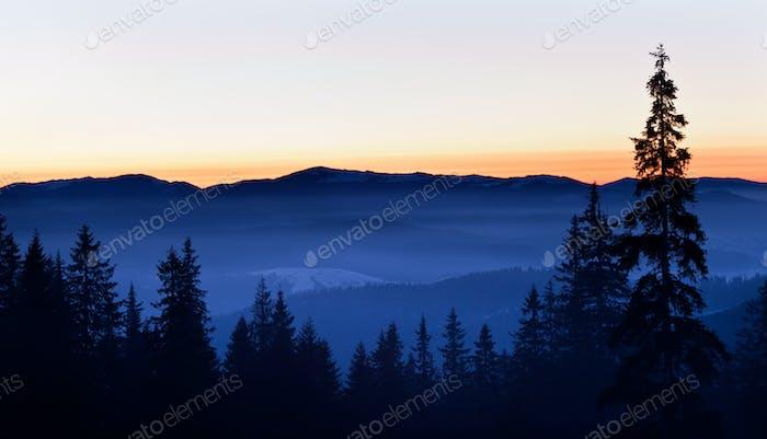 Panoramablick auf Winterhügel und Tal bedeckt mit Schnee und weißem Rauch