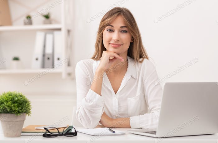 Business Lady Sitting At Laptop Looking At Camera In Office