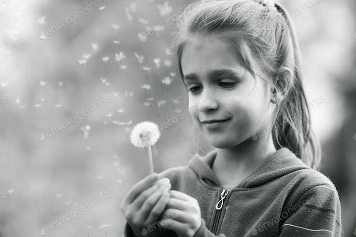 Kleine schöne Mädchen hält Feder Löwenzahn in der Hand