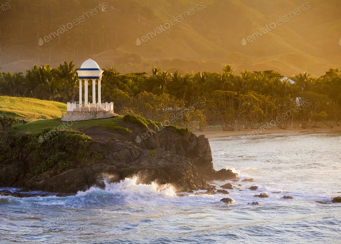 Gazebo and palm trees along the shore in the Caribbean Sea.