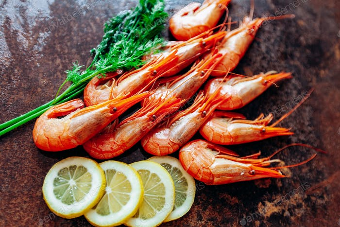 Fresh shrimp with lemon and dill on the red table.