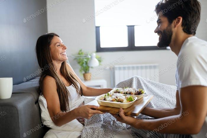 Loving couple having breakfast in bed. Loving couple. Family relationships