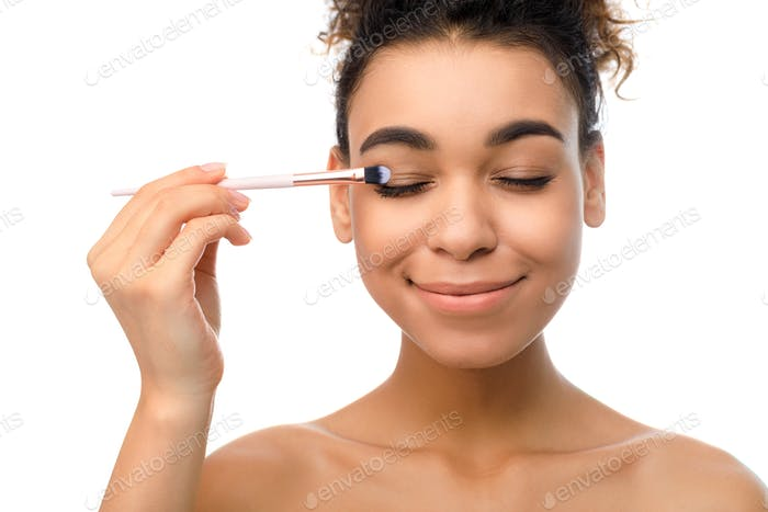Makeup for eyes. Afro woman applying eyeshadow herself