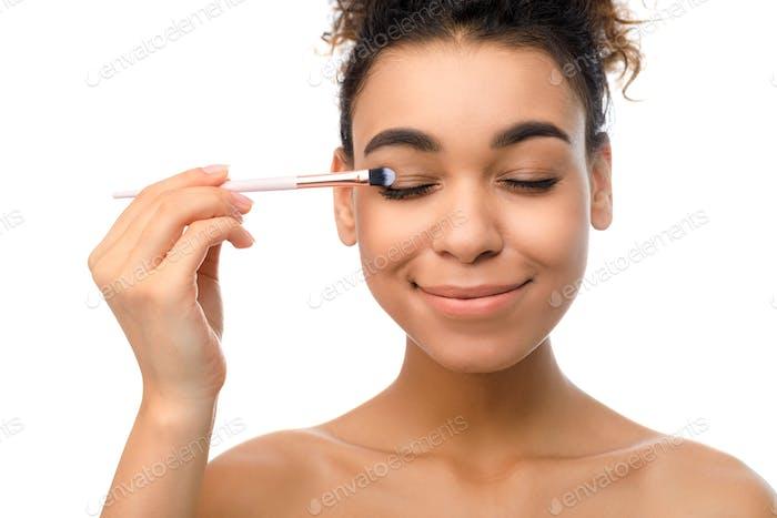 Make-up für Augen. Afro Frau Anwendung Lidschatten selbst
