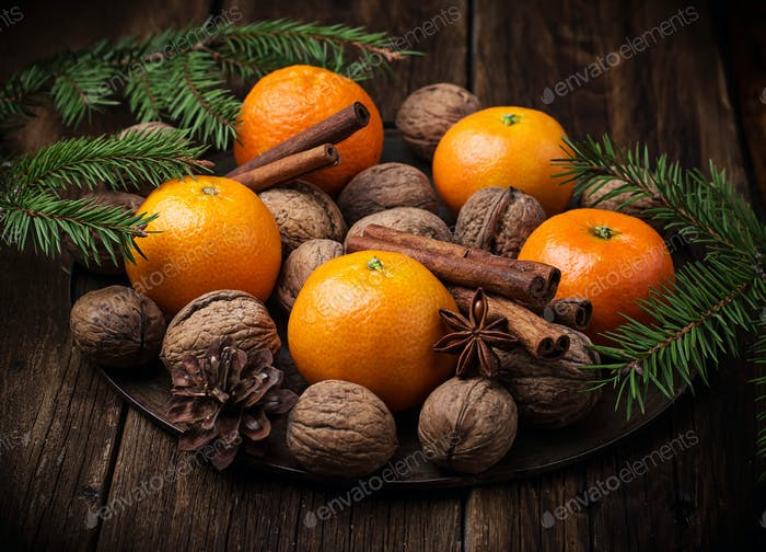 Christmas composition with tangerines, nuts and cinnamon