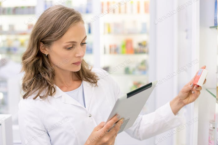 Young pharmacist with touchpad checking or looking for medicine in computer base