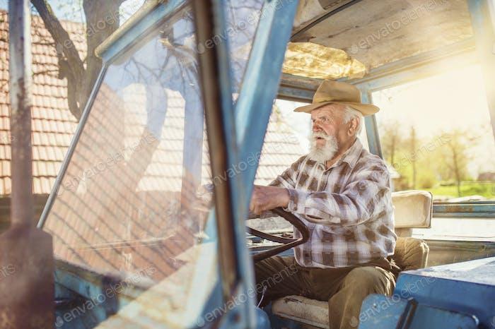 Senior Landwirt auf einem Traktor