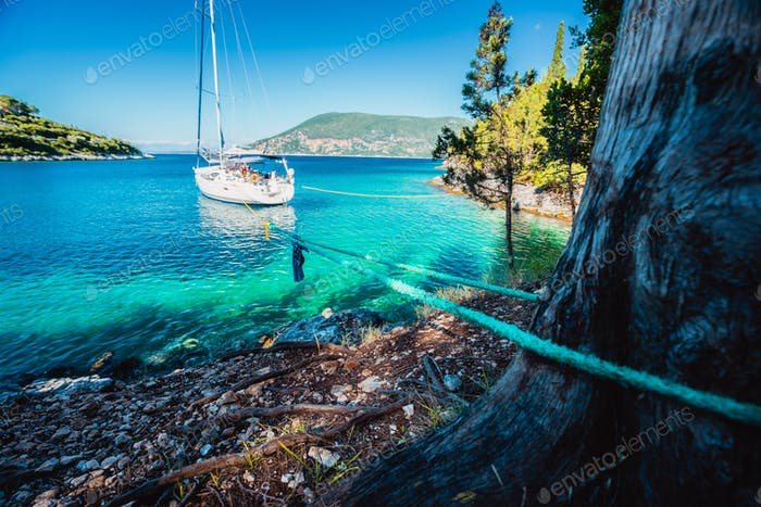 Sail boat docked alone in emerald hidden lagoon among picturesque mediterranean nature Ionian
