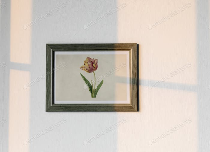 Flower photo frame hanging on white wall