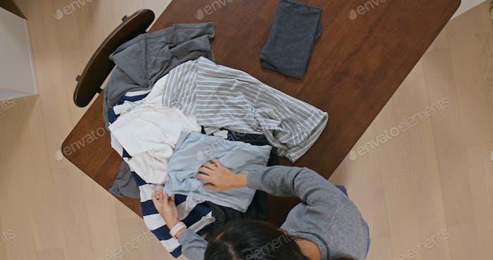 Женщина складывать одежду дома