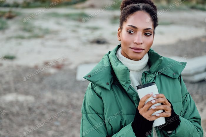Beautiful African American girl in down jacket holding cup to go dreamily looking away outdoor