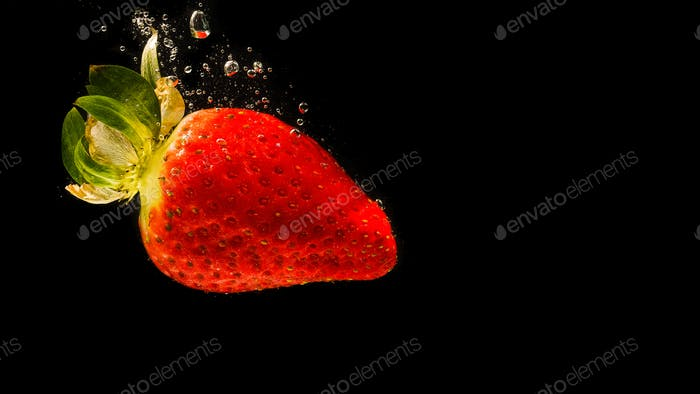 Strawberry falling into water causing bubbles all around it. Healthy food concept