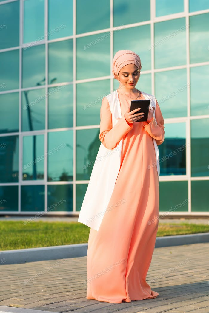 pretty modern Arabian woman with tablet computer outdoors
