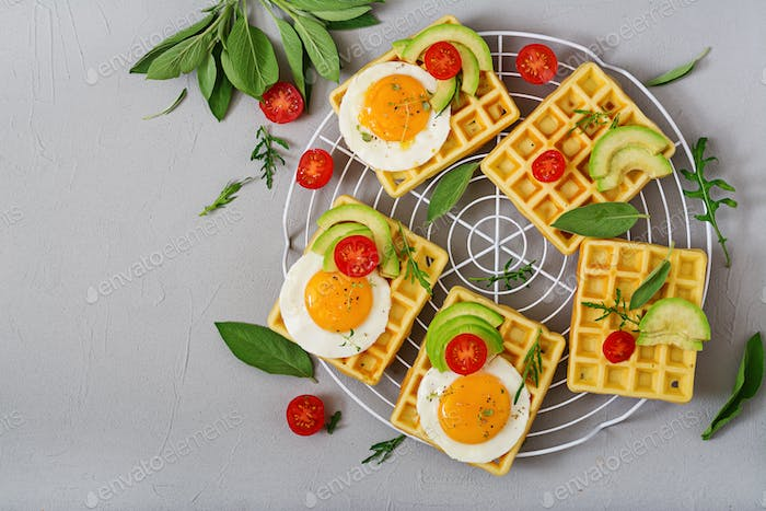 Healthy breakfast - waffles, eggs, avocado, tomatoes and herbs. Flat lay. Top view