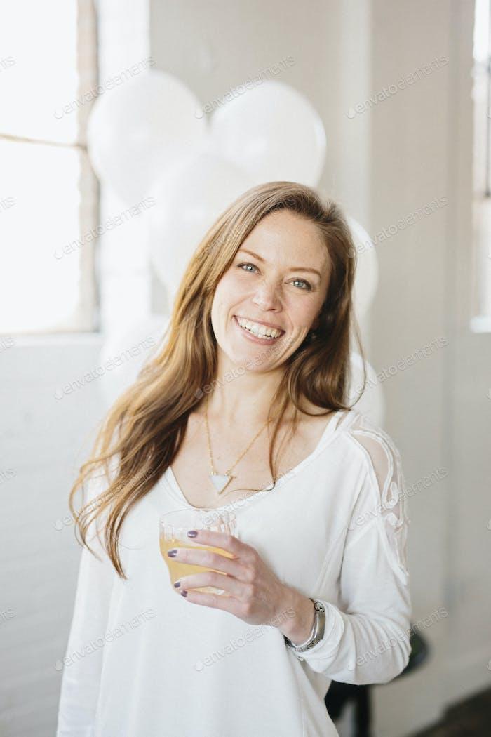Eine Frau mit langen Haaren in einer weißen Bluse, die einen Drink hält. Weiße Luftballons, Partydeko