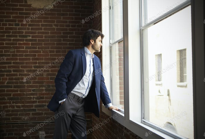 Businessman Standing By Office Window