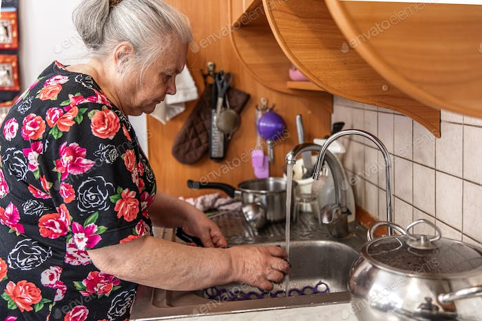 A woman aged in a dressing gown washes the dishes.
