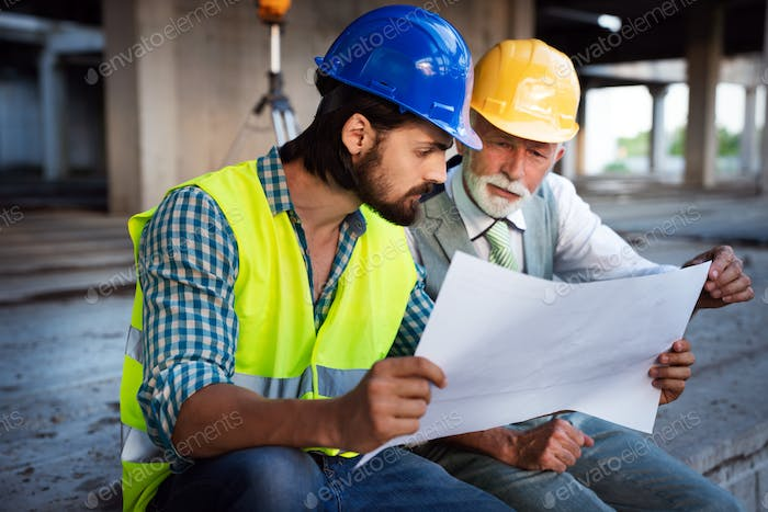 Male architects analyzing blueprint at construction site