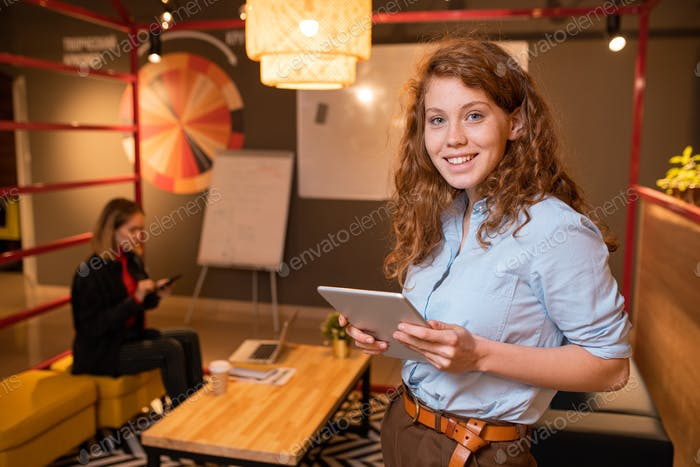Young cheerful office manager with digital tablet standing in front of camera