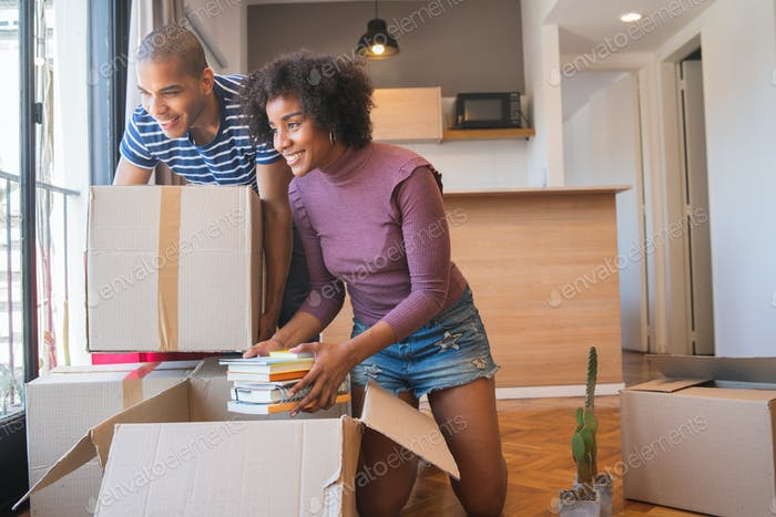 Latin couple unpacking at their new house.
