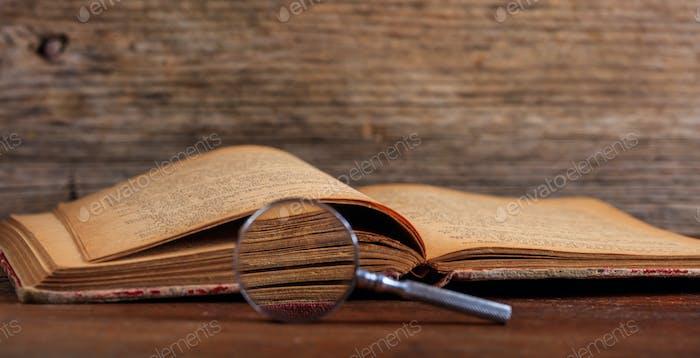 Vintage-Buch und Lupe auf Holzschreibtisch