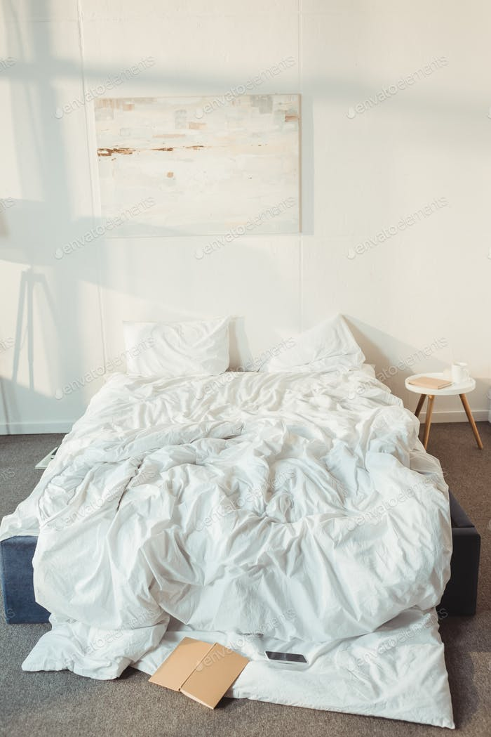 interior of modern bedroom at morning with mess on bed