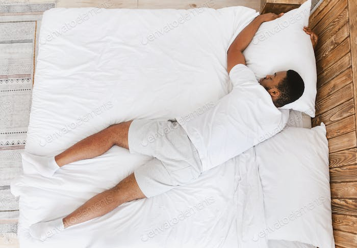 Unrecognizable Black Guy Sleeping Lying On Stomach In Bed Indoor