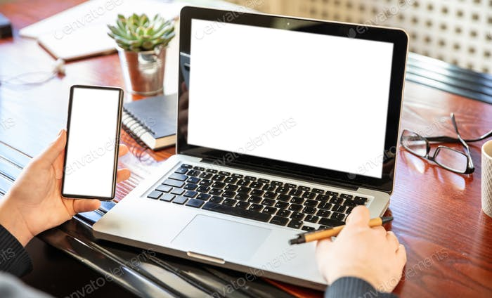 Laptop and smartphone with white blank screens, office interior background