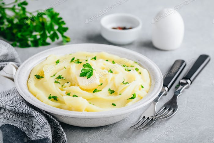 Mashed Potatoes with butter and fresh parsley in a white bowl on gray stone background.
