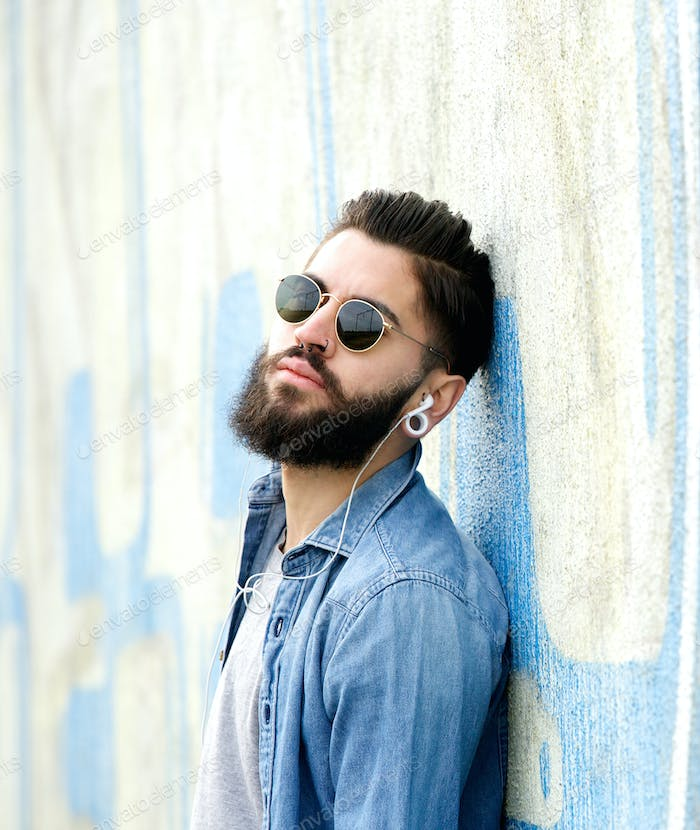 Cool guy with beard listening to music with earphones
