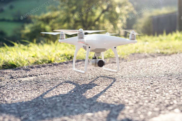 Flying helicopter drone with camera. Green sunny nature.