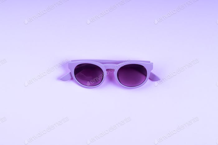 Ultra violet sun glasses on monochrome backdrop