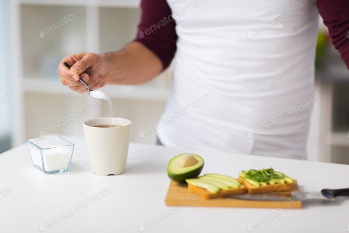man having breakfast and adding sugar to coffee