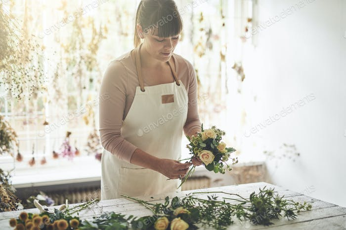 Female florist arranging flowers at a table in her shop