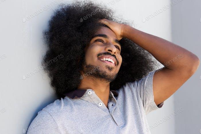 смеясь афро человек с рукой в волосах глядя