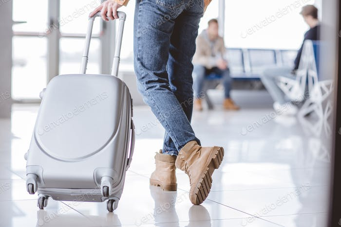 low section young young traveler with suitcase in airport terminal