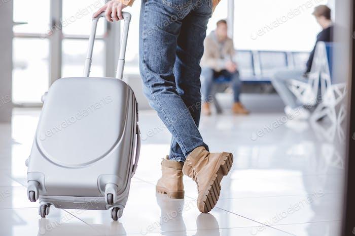sección baja joven viajero joven con maleta en terminal del aeropuerto