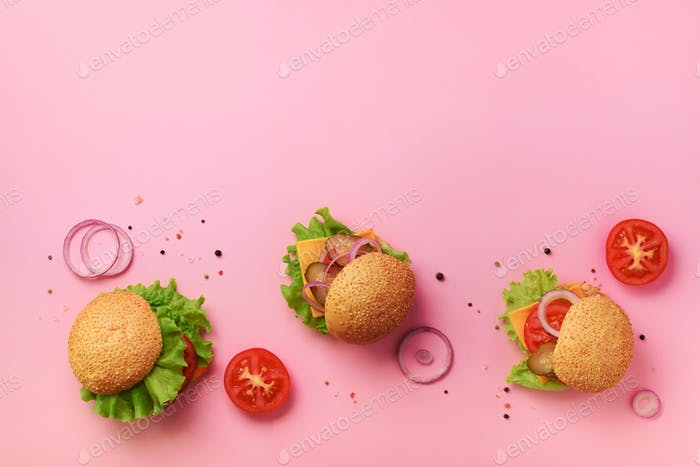 Tasty burgers with beef, tomato, cheese, onion, cucumber and lettuce on pink background. Top view