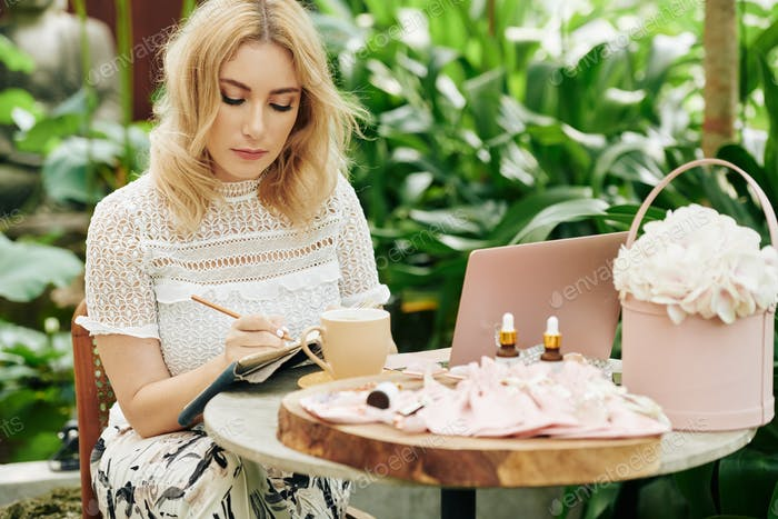 Female entrepreneur writing business plan