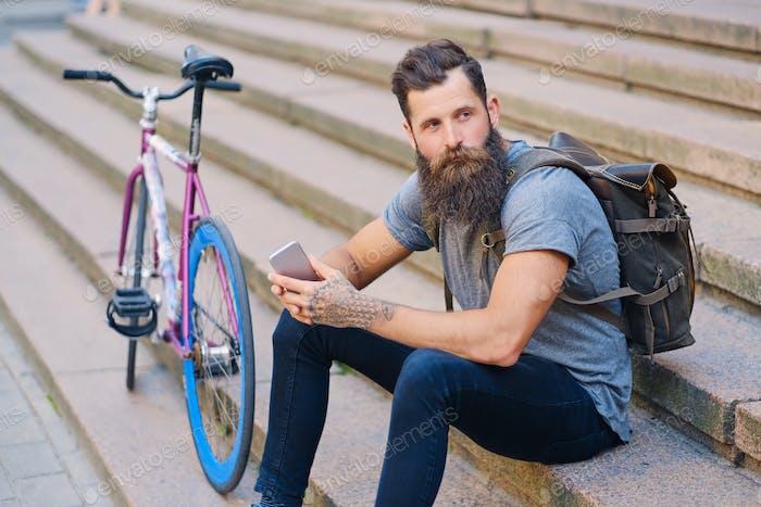 Ein Mann sitzt auf einer Stufe und benutzt ein Smartphone.