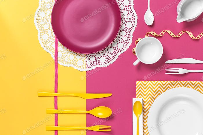 Colorful dishes on a yellow rose table. Stylish arrangement.