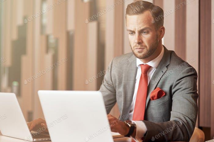 Confiado guapo negociosmna sentado en la mesa