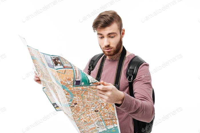 Portrait of cool boy standing with road map in hands and black backpack isolated
