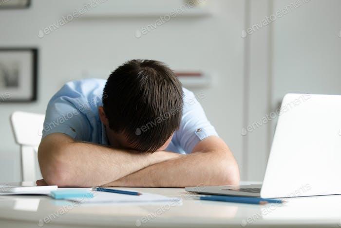 Vertical de un Hombre acostado en escritorio cerca de Ordenador portátil