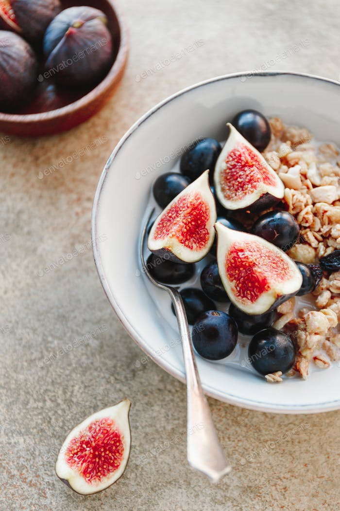 Close-up view of a breakfast bowl with granola, blue grape and fig slices